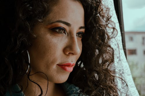 Headshot of calm ethnic female with curly hair looking away standing near window in sunlight