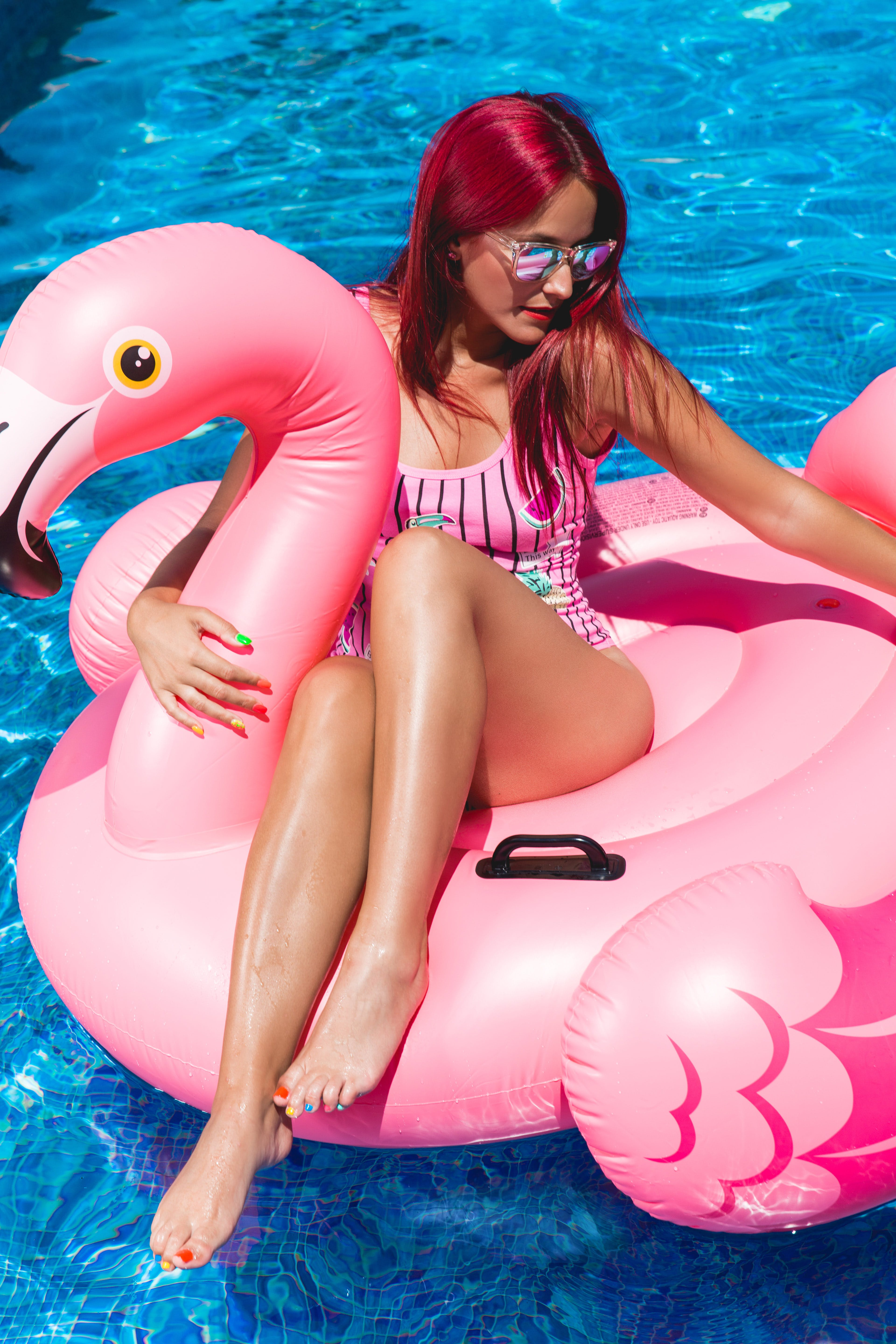 Woman Sitting on Flamingo Inflatable Floater