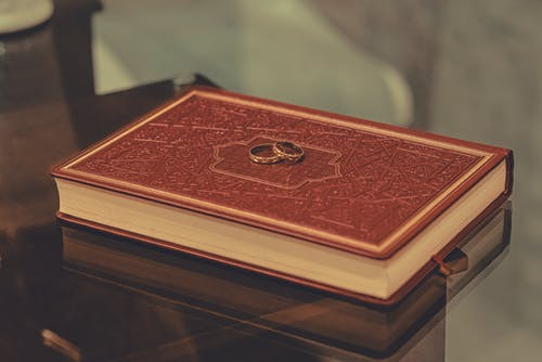 Composition of golden rings placed on red ornamental book placed on glass table