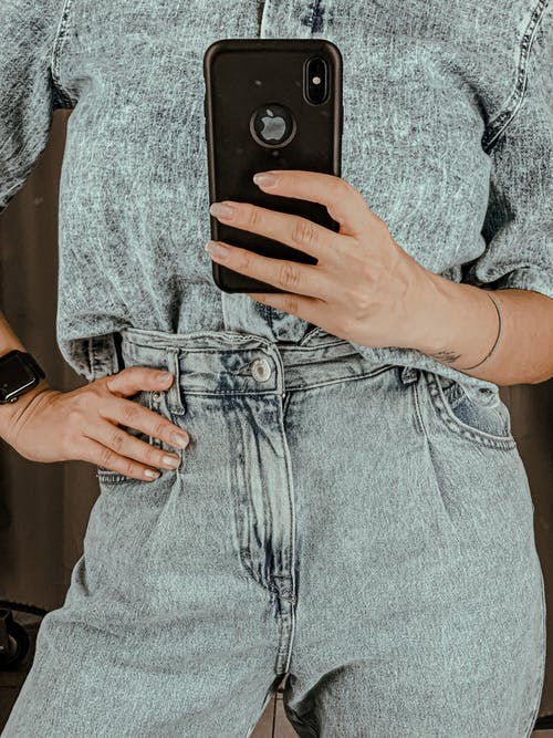 Crop woman in denim taking selfie with smartphone