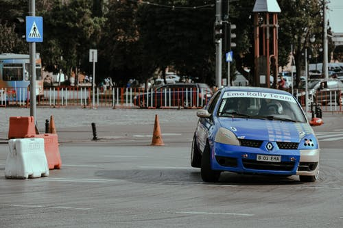 Blue colored racing car taking part in rally competition and driving on central street