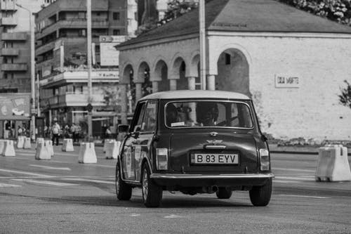 Black and white of small vintage car driving on empty city street in daylight