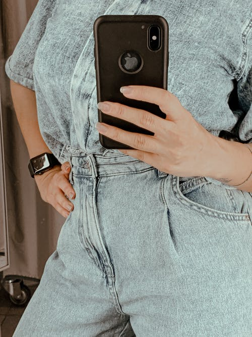 Crop lady wearing stylish blue t shirt with denim using smartphone to take selfie