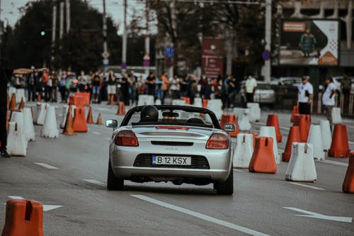 Stylish silver cabriolet driving fast among barriers on city street with viewers on background