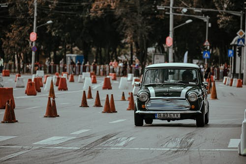 Black old timer car driving on racetrack of city street while taking part in rally