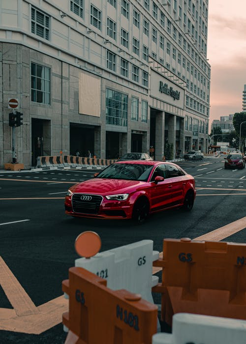 Contemporary red car driving in urban city district