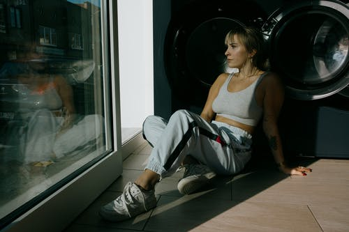Woman in White Tank Top and Gray Pants Sitting on Floor