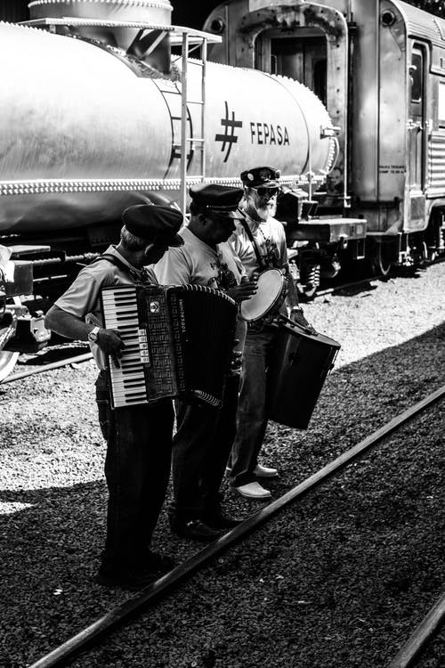 Grayscale Photo of Men Standing while Playing Musical Instrument Near a Railway