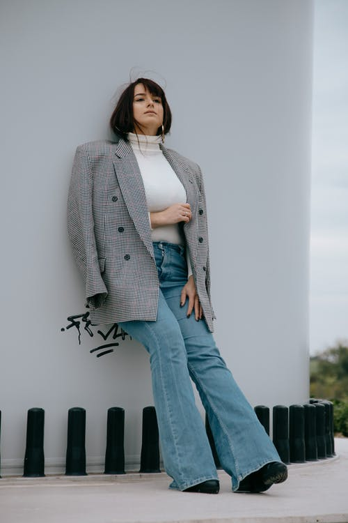 Full body of stylish female wearing trendy jacket and jeans leaning on white wall while looking up