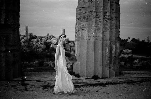 Grayscale Photo of Woman in White Wedding Dress Standing Near Concrete Pillar