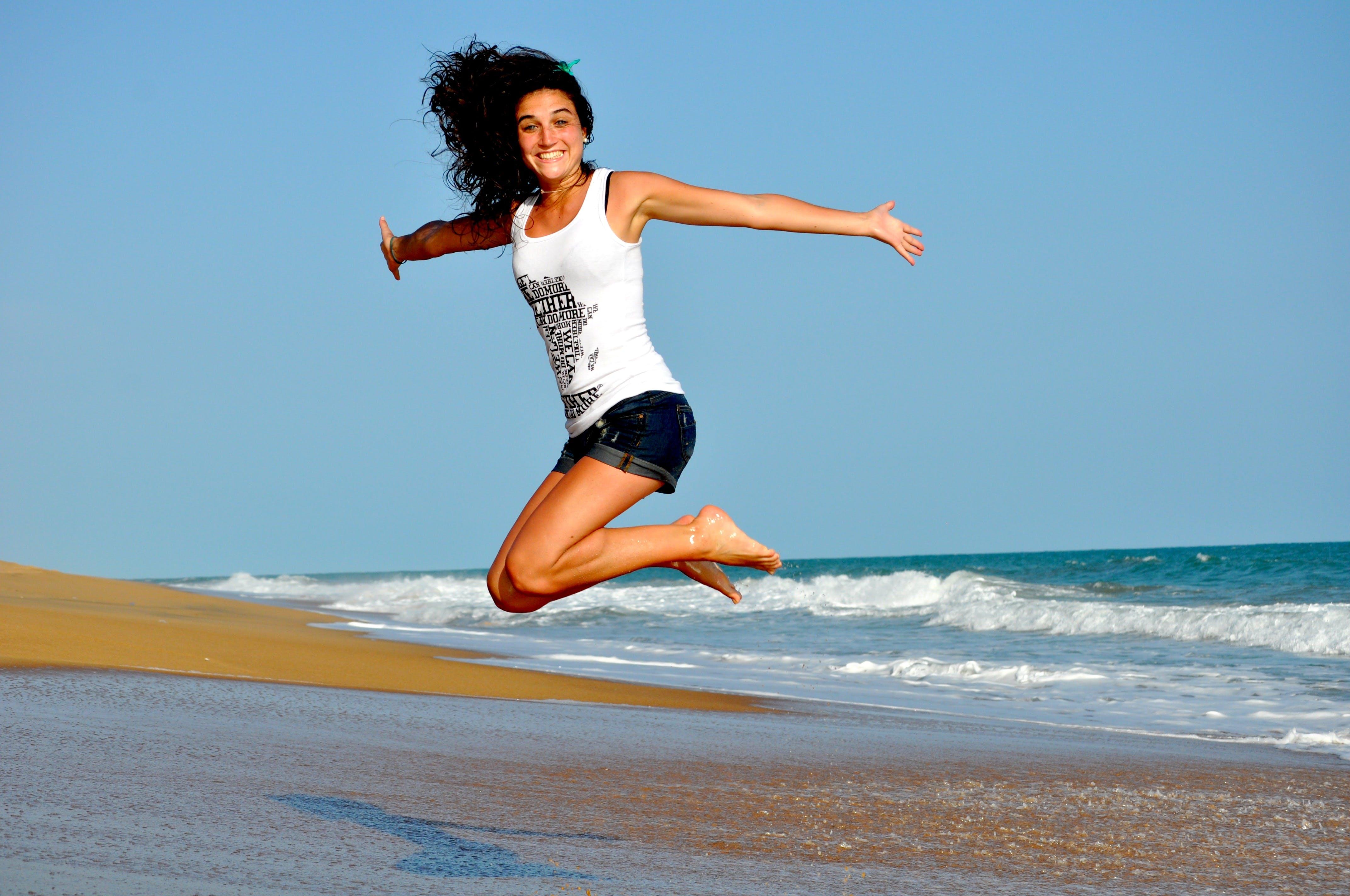Woman in White Tanktop Jump over Beach Sand