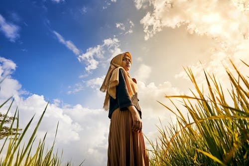 Woman in Brown Hijab Standing on Green Grass Field Under Blue and White Sunny Cloudy Sky