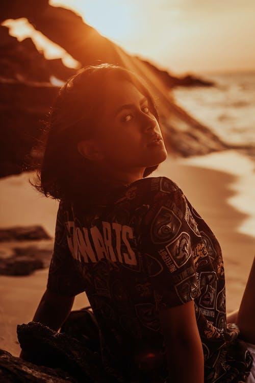 Stylish dreamy ethnic woman on sea beach at sunset