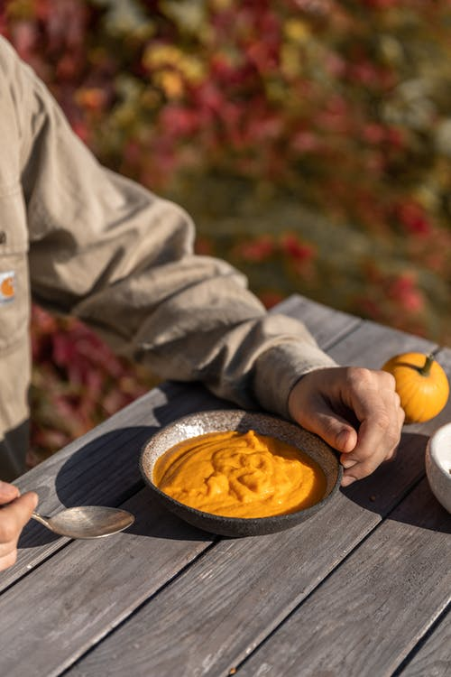 Person in Gray Jacket Holding a Stainless Steel Fork With Yellow Sauce