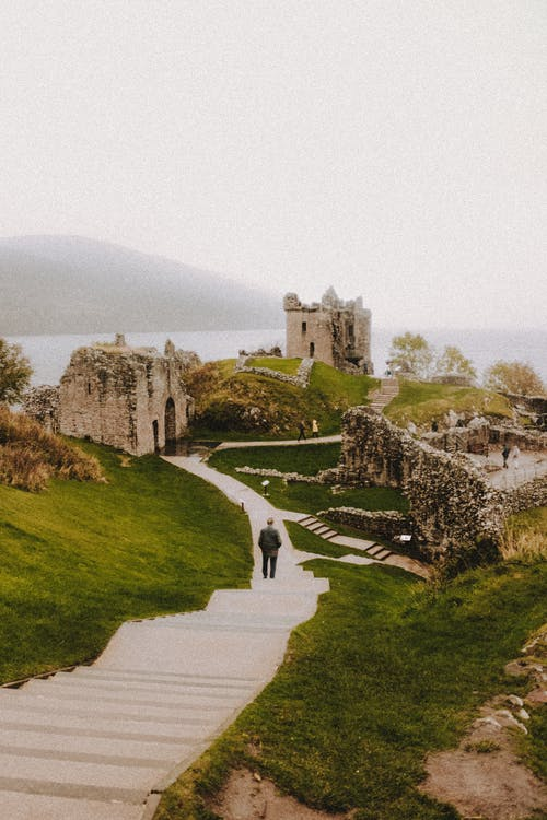 Anonymous tourist on stairs contemplating old ruined castle on mount