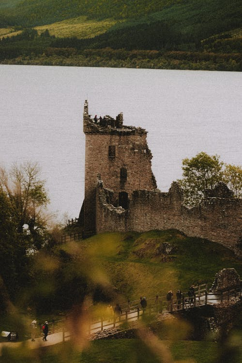 From above of aged partially destroyed castle facade on green mount near bridge with unrecognizable travelers