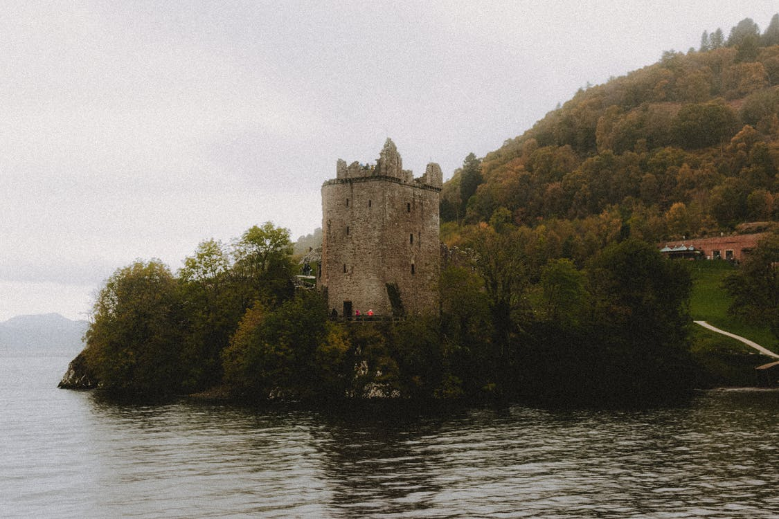 Scenic view of ancient masonry castle exterior on mountain with trees near Loch Ness lake under misty sky