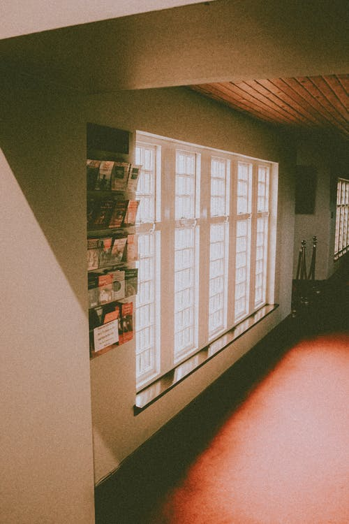 Contemporary building with empty passage near window and shelf with assorted flyers in sunlight