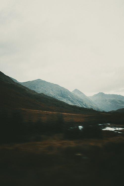 Lake Near Mountains Under White Sky