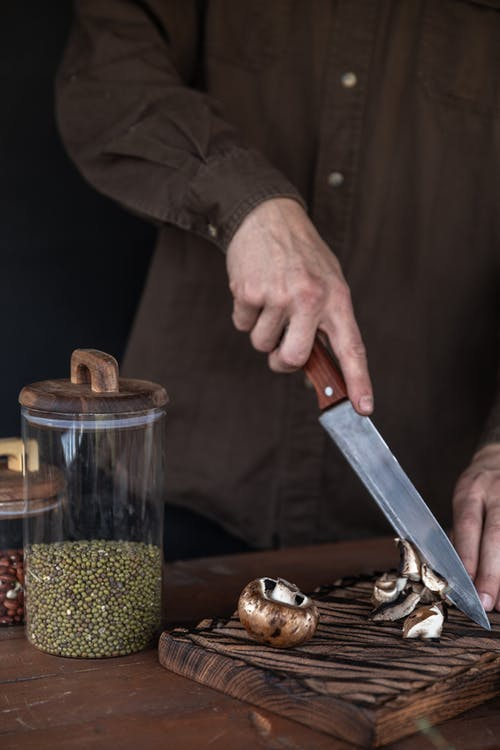 Person Holding a Knife and Slicing Mushrooms in a Wooden Chopping Board