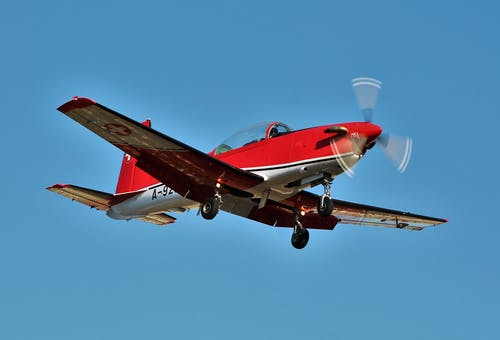 Modern aircraft with propeller and stepped tandem cockpit flying in blue sky