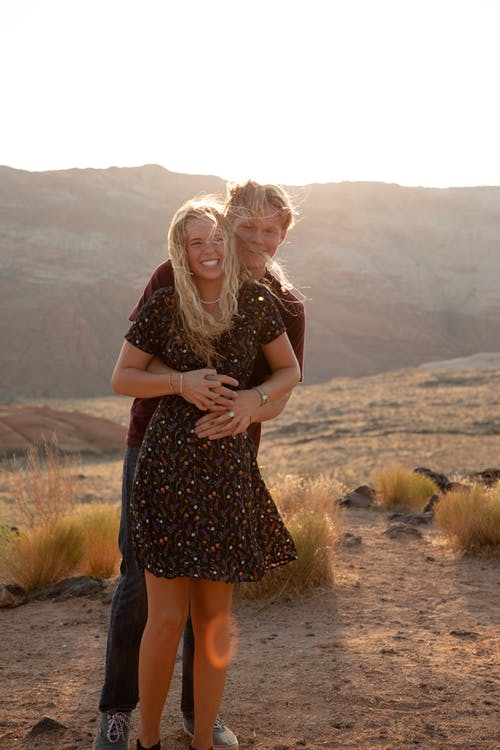Content man embracing cheerful girlfriend in desert behind mount