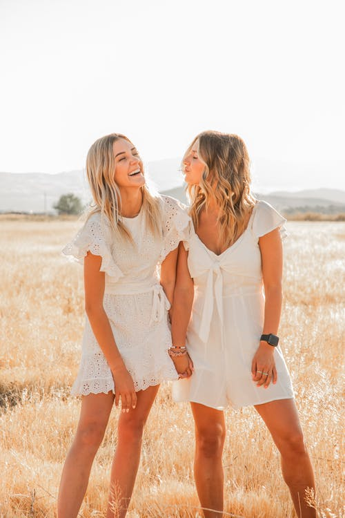 Young cheerful female holding hand of best friend with pouting lips on grass meadow under white sky in back lit