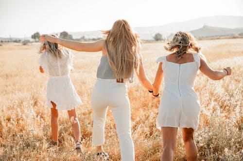 Faceless trendy women having fun on grass meadow in summer
