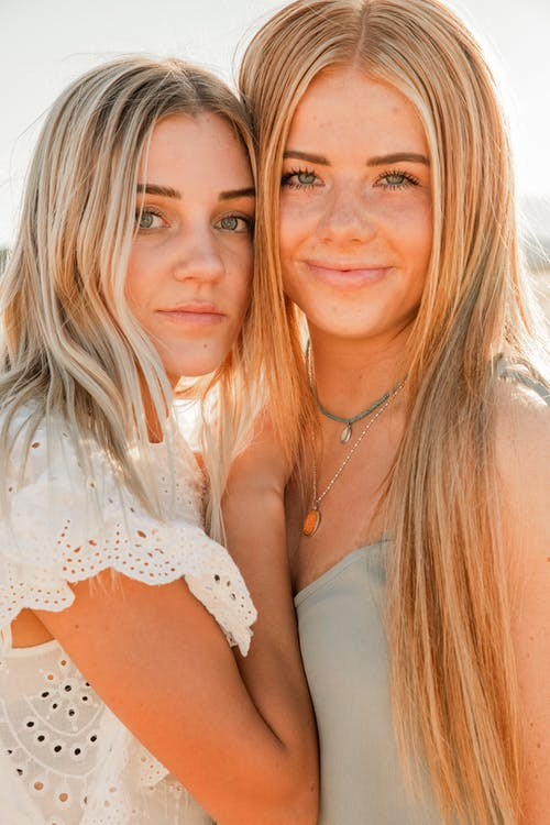 Young attentive woman in trendy wear standing close to crop content girlfriend in accessories while looking at camera in back lit