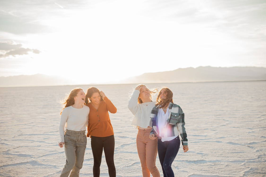 Excited girlfriends in trendy wear in desert under shiny sky