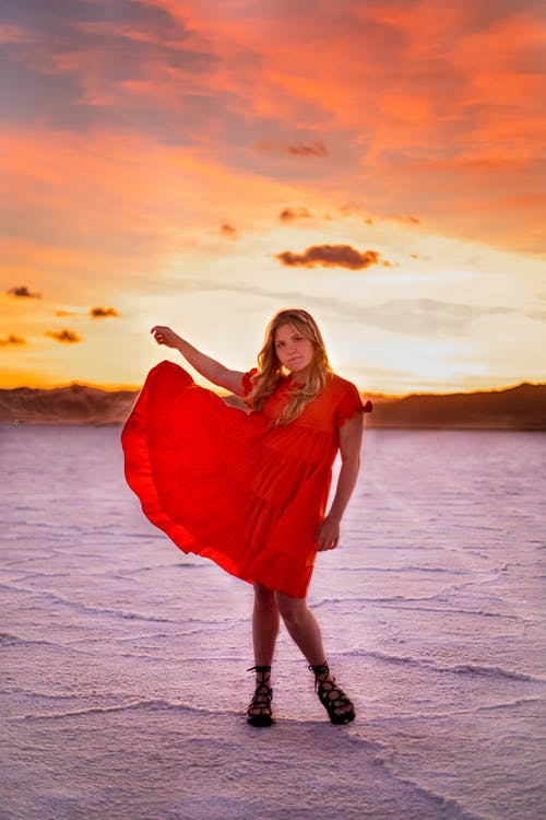 Young female in bright flying dress standing with raised arm in desert under cloudy sky at sunset while looking at camera