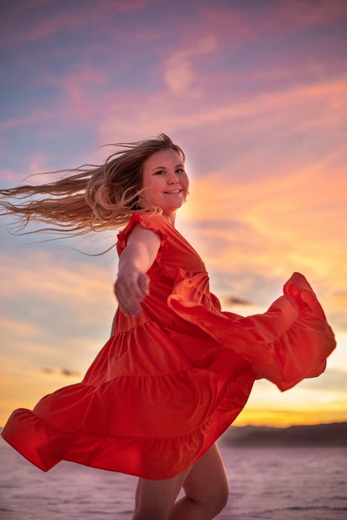 Smiling woman in flying red dress at sunset
