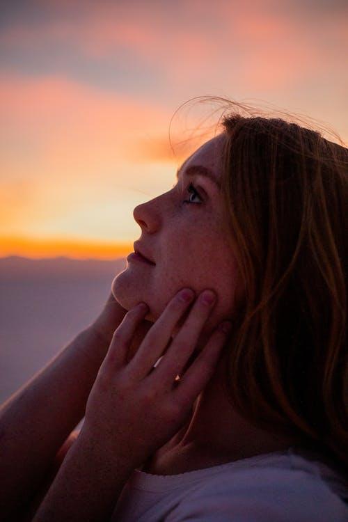 Crop charming dreamy woman enjoying sunset in mountains