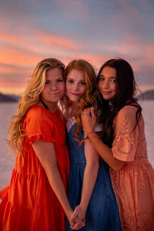 Young cheerful women in bright trendy apparel looking at camera under cloudy sky at sundown