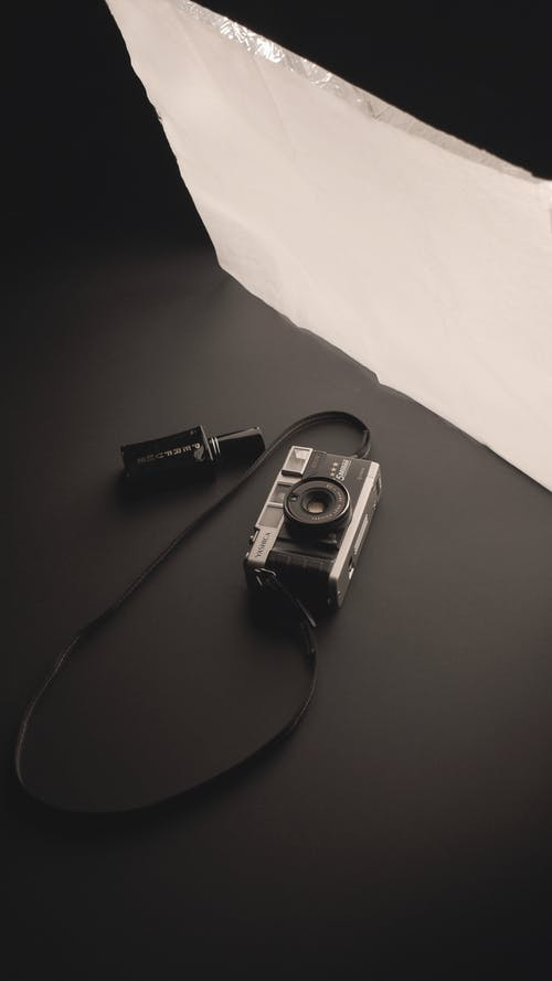 High angle of professional photo camera near glass on gray surface in studio