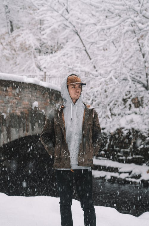 Adult man in hoodie and jacket standing in nature in heavy snowfall and looking away