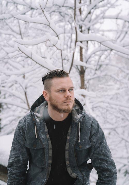 Brutal man standing in heavy snowfall