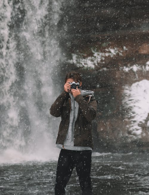 Man taking photo at waterfall in winter
