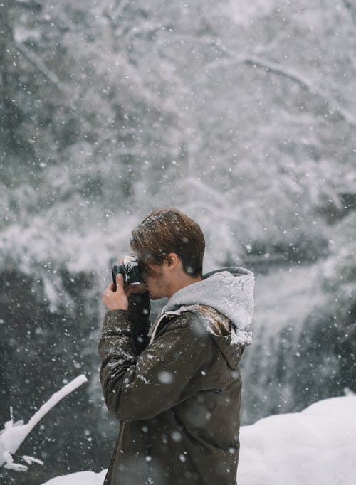 Side view of hipster guy with photo camera taking shot of snowy landscape in nature