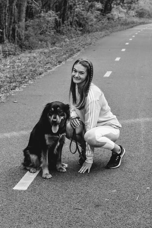 Woman in Long Sleeve Shirt Holding Black and Brown Short Coated Dog