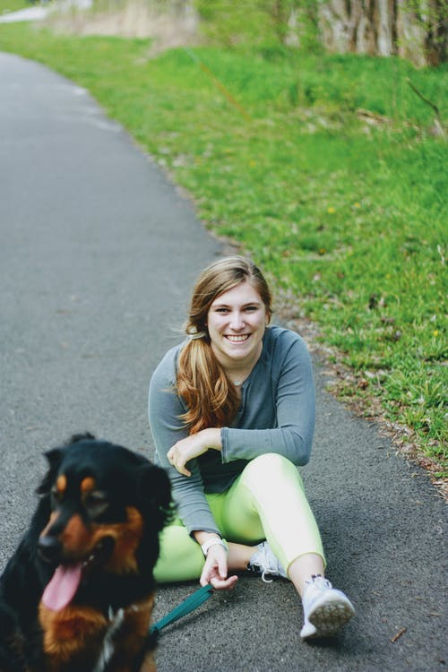 Woman in Gray Long Sleeve Shirt and Green Pants Sitting on Green Grass Field Beside Black