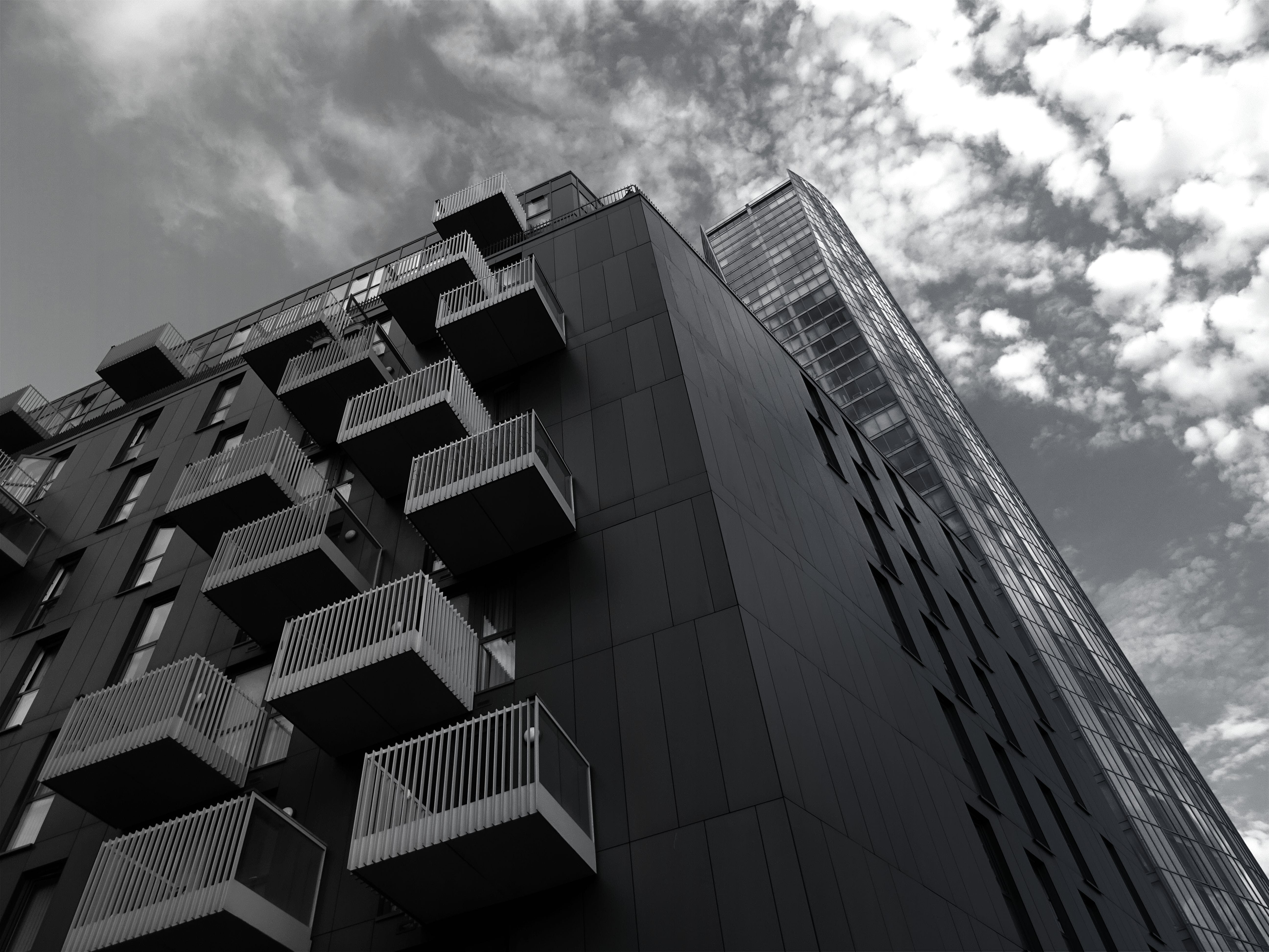 Grayscale and Low Angle Photography of High-rise Building Structure