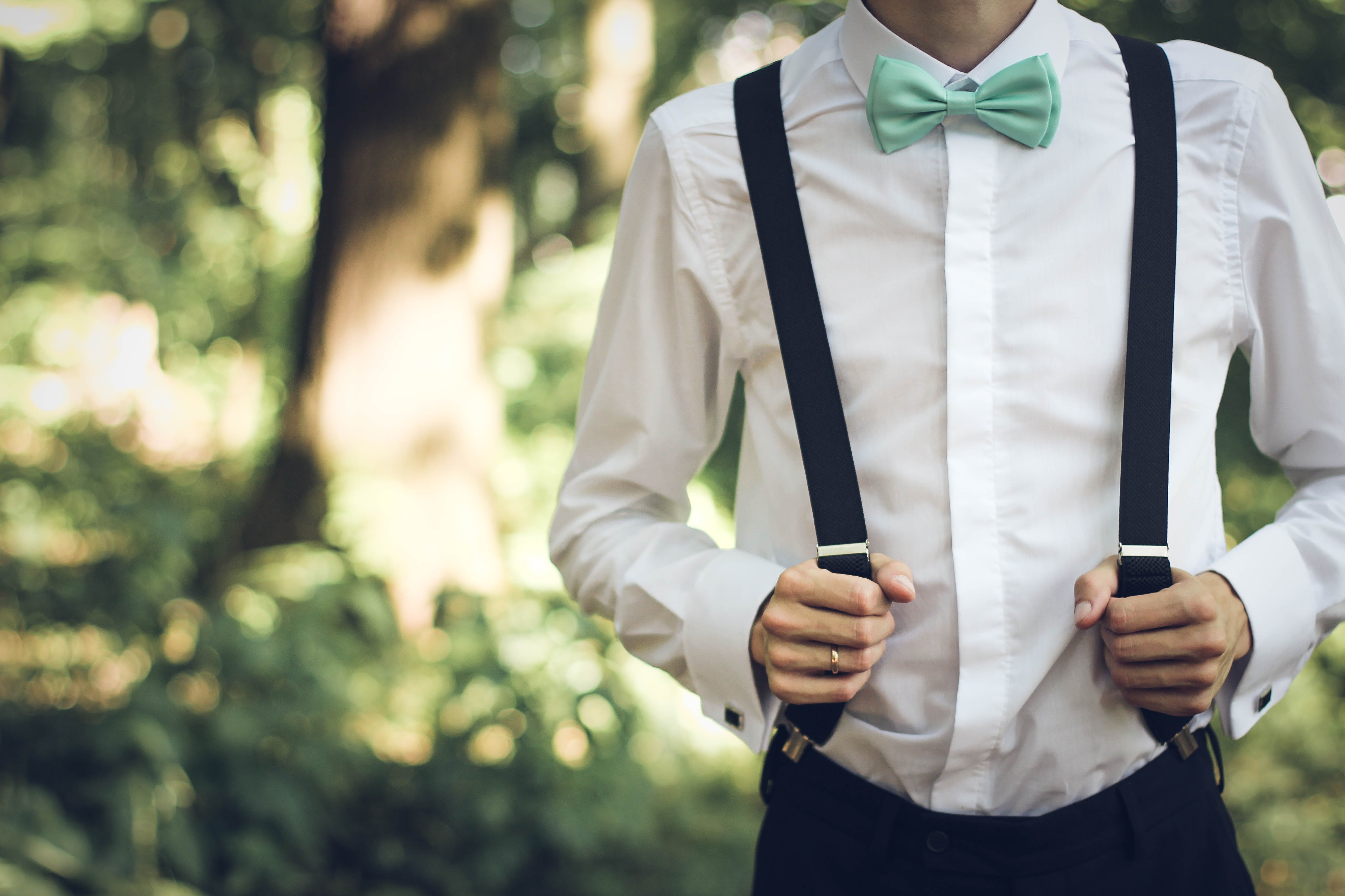Person Holding Black Suspenders