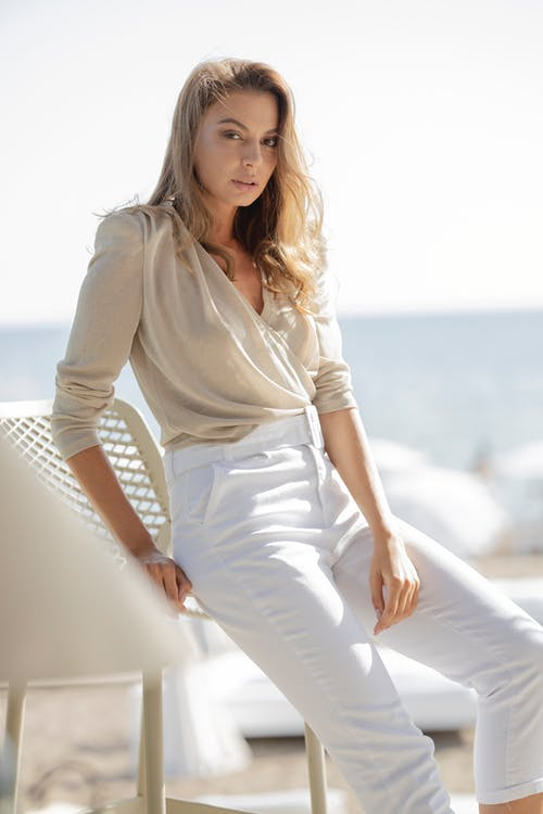 Woman in White Long Sleeve Shirt and White Pants Sitting on White Concrete Railings