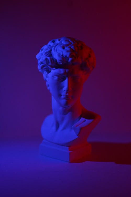 Bust of young male on plinth placed on white surface in dark studio in blue and red lights