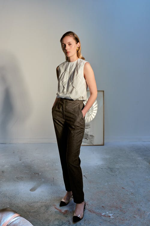 Woman in White Tank Top and Black Pants Standing Beside White Wall