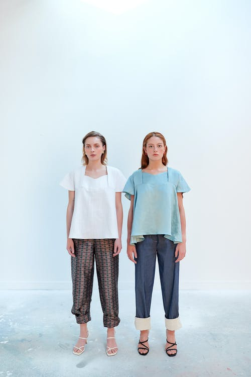 2 Women in White and Teal Shirts Standing Beside White Wall