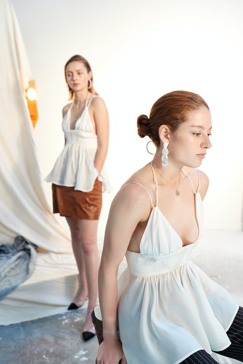 Woman in White Spaghetti Strap Dress Standing on White Floor