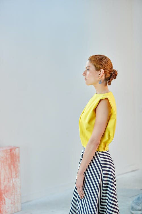 Woman in Yellow Long Sleeve Shirt and Black and White Striped Skirt