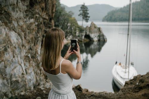 Woman in White Tank Top Taking Photo of Lake